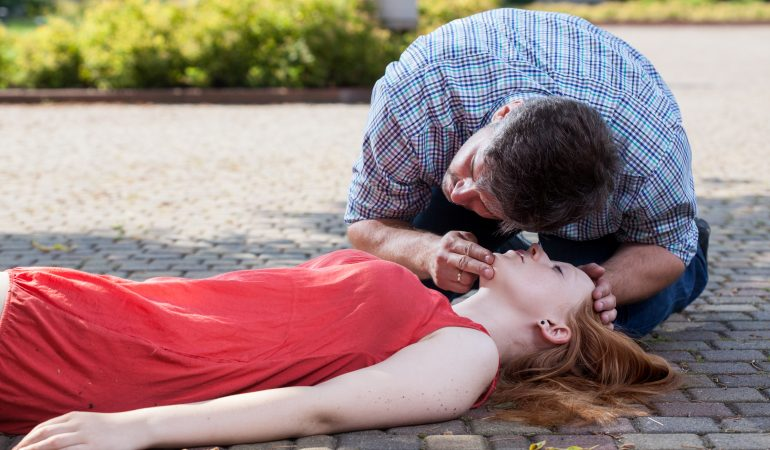 View of man checking if woman's conscious