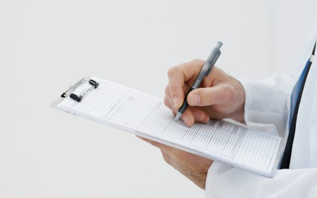 Close-up mid section of a doctor holding clipboard